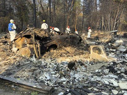 Volunteer members of an El Dorado County search and rescue team search the ruins of a home and vehicle, looking for human remains, in Paradise, Calif., Nov. 18, 2018, following a Northern California wildfire.