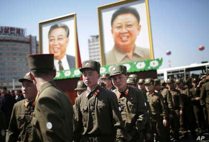 North Korean soldiers walk in the Ryomyong residential area, a collection of more than a dozen apartment buildings, after attending its official opening ceremony, while portraits of the late leaders Kim Il Sung and Kim Jong Il are seen at rear on Apr...
