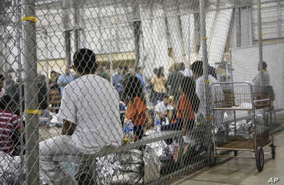 FILE - A photo provided by U.S. Customs and Border Protection shows people taken into custody related to cases of illegal entry into the United States, at a facility in McAllen, Texas, June 17, 2018.