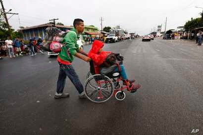 Nicaraguan migrant Javier Velazquez wheels his 14-year-old son across a highway, as part of the Central American migrant caravan hoping to reach the U.S. border, in Acayucan, Veracruz state, Mexico, Nov. 3, 2018. Javier Velazquez  said that Axel was