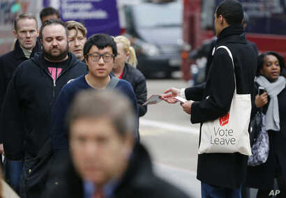 FILE - A Pro-Brexit campaigner hands out leaflets at Liverpool Street station in London, March 23, 2016. Following right-wing election gains, Eurosceptics in Austria and Poland are keeping a close eye on Britain's June 23rd referendum to stay or qu...