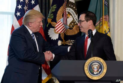 President Donald Trump shakes hands with Treasury Secretary Steven Mnuchin at the Treasury Department in Washington, April 21, 2017, where the president signed an executive order to review tax regulations set last year by his predecessor, as well as