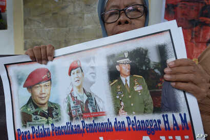 """FILE - An Indonesian protester holds a placard featuring Prabowo Subianto, center, reads, """"Doers kidnapping, killing and human rights violators"""" during a protest against presidential candidate Prabowo Subianto in Jakarta, Indonesia, May 20, 2014. For..."""