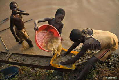 FILE - Boys pan for gold on a riverside at Iga Barriere, 25 km (15 miles) from Bunia, in the resource-rich Ituri region of eastern Congo, Feb. 16, 2009.