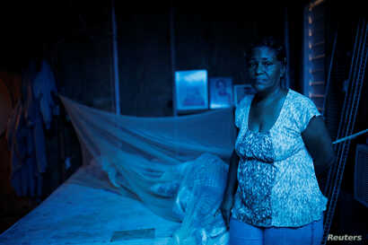 Milagros Jimenez poses for a picture at her house, which was partially destroyed by Hurricane Maria, at the squatter community of Villa Hugo in Canovanas, Puerto Rico, Dec. 9, 2017.