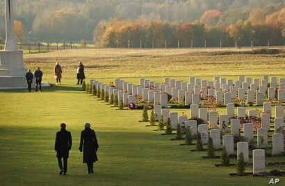 British Prime Minister Theresa May and French President Emmanuel Macron walk together after laying wreaths at the World War I Thiepval Memorial in Thiepval, France, Nov. 9, 2018. The memorial commemorates more than 72,000 men of British and South Afr...