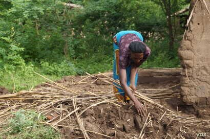Agness Milonje, a flood victim in southern Malawi, collects pieces of her flood-damaged home.
