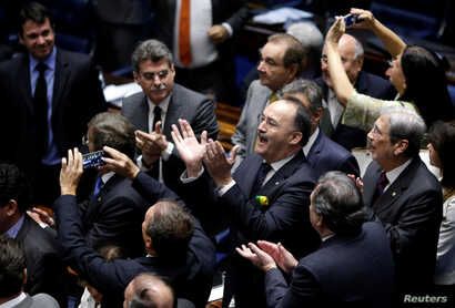 Members of Brazil's Senate react after a vote to impeach President Dilma Rousseff for breaking budget laws in Brasilia, Brazil, May 12, 2016.