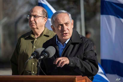 Israel's Prime Minister Benjamin Netanyahu stands with Defense Minister Moshe Yaalon (l) during a visit to an army base near the Gush Etzion bloc of Jewish settlements in the West Bank, Nov. 23, 2015.