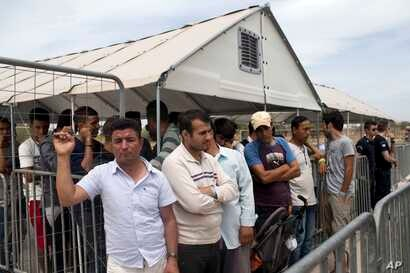 FILE - In this file photo taken on Monday, June 13, 2016, migrants who live in the Hellenikon refugee and migrant camp in  Athens wait to register for asylum. A government official in Athens on Wednesday, Aug. 3, 2106 said to the Associated Press tha...