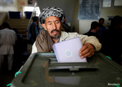 FILE - An Afghan man casts his vote during the parliamentary election at a polling station in Kabul, Oct. 21, 2018.
