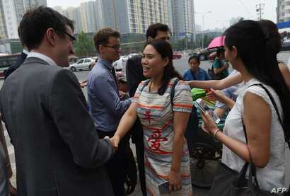Fan Lili (C), the wife of detained activist Gou Hongguo, and other wives of detained layers meets with foreign diplomats near an office of the Supreme People's Procuratorate after attempting to hand in a formal complaint about being denied access t...