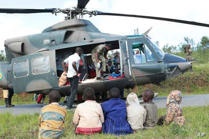 Soldiers and paramedics carry injured people from a helicopter in Chimanimani, about 600 kilometers south east of Harare, Zimbabwe, March, 19, 2019.
