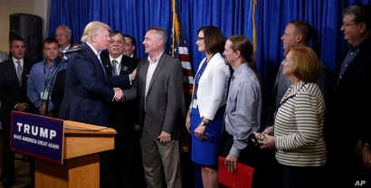 Republican presidential candidate Donald Trump, right, greets some of the 22 delegates from North Dakota to the Republican National Convention, who are the core of delegates that elevated Trump over the 1,237 needed for the GOP's presidential nominat...