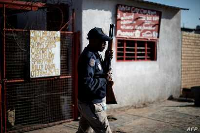 FILE - A South African police officer holds a rifle as he stands in Soweto, Johannesburg, Aug. 29, 2018, during unrest that erupted after a foreign shop owner allegedly shot and killed a member of the community during a demonstration.