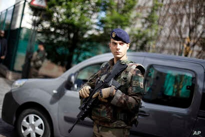A French soldier stands near the scene where soldiers were hit and injured by a vehicle in the western Paris suburb of Levallois-Perret near Paris, France, Aug. 9, 2017.