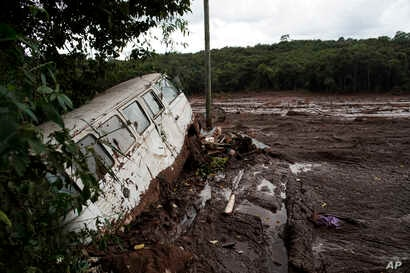 A van is seen in half buried in the mud after a dam collapse near Brumadinho, Brazil, Jan. 26, 2019. Rescuers in helicopters on Saturday searched for survivors while firefighters dug through mud in a huge area in southeastern Brazil buried by the col...