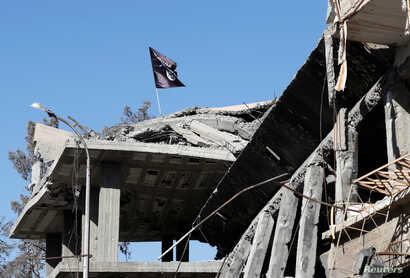 A flag of Islamic State militants is pictured above a destroyed house near the Clock Square in Raqqa, Syria, Oct.18, 2017.