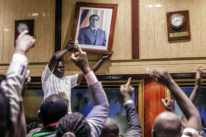 People remove, from the wall at the International Conference centre, where parliament had their sitting, the portrait of former Zimbabwean President Robert Mugabe after his resignation, Nov. 21, 2017 in Harare.