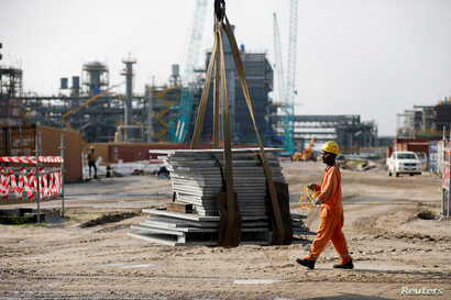 A construction worker assists with moving building materials on a lift at the Dangote Oil Refinery under construction, in Ibeju Lekki district, on the outskirts of Lagos, Nigeria, July 5, 2018.