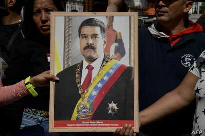 Supporters of Venezuelan President Nicolas Maduro hold a portrait of him in a ceremony to swear him in symbolically in front of the National Assembly building during a rally around the city in Caracas, Jan. 7, 2019.
