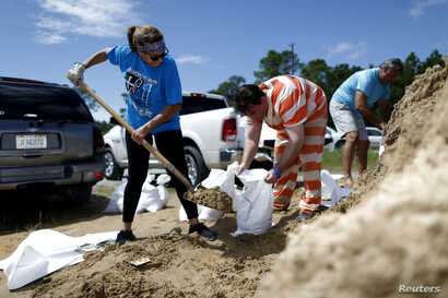 An inmate with the Hancock County Department of Corrections helps Janice Labat fill a bag with sand as Tropical Storm Gordon approaches Bay St. Louis, Mississippi, Sept. 4, 2018.