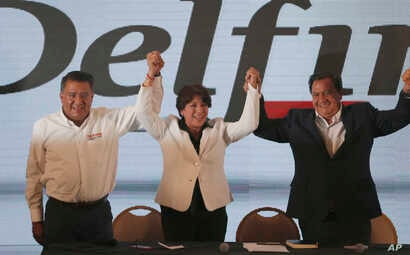 Schoolteacher-turned-politician and Mexico state gubernatorial candidate for the National Regeneration Movement, or MORENA, Delfina Gomez, center, greets supporters at her party's headquarters in Toluca, Mexico, June 4, 2017.