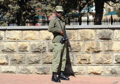 FILE - A soldier stands outside the military headquarters in Maseru, Lesotho, Aug. 31, 2014. Prime Minister Thomas Thabane said there had been an attempt to take over Lesotho, a country of about 2 million people that is surrounded by South Africa.