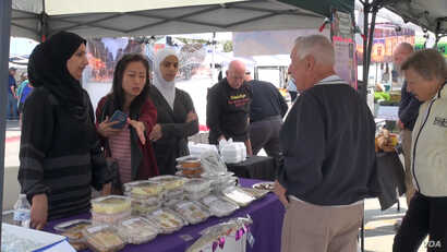 Noor al Mousa sells Syrian sweets as Tan Jakwani and an interpreter help at a farmers market in Phoenix, Arizona.