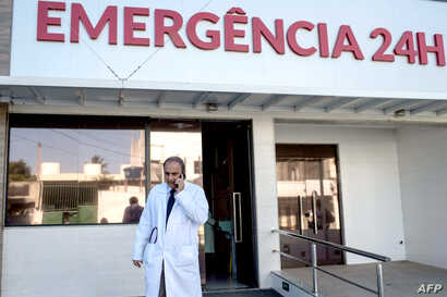 Brazilian infectologist Antonio  Bandeira, who was part of the team of researchers who identified the Zika virus in Brazil, talks by mobile in front of the Santa Helena hospital in Camaçari, Bahia, Brazil  on Jan. 29, 2016, Brazil. Brazilian Preside...