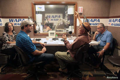 People talk during a show at the WAPA 680 radio station, in San Juan, Puerto Rico, Sept. 27, 2017.