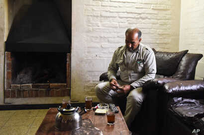 FILE - Merhi Alshebli rolls a cigarette in his living room in Juan Lacaze, Uruguay. In November 2014, locals welcomed Alshebli, his wife and their 15 children, who were fleeing Syria's civil war. The family later complained they couldn't make ends me...
