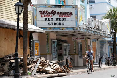 FILE - A cyclist rides past a pile of debris, Sept. 21, 2017, in Key West, Fla.