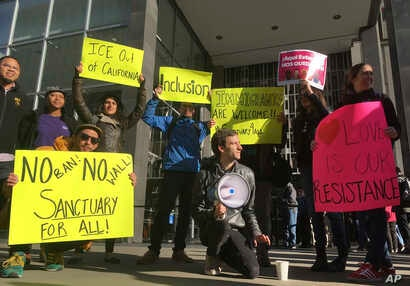 Protesters hold up signs outside a courthouse, April 14, 2017, where U.S. District Court Judge William Orrick ruled on a lawsuit challenging President Donald Trump's executive order to withhold funding from sanctuary cities.
