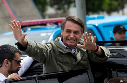 Jair Bolsonaro, presidential candidate with the Social Liberal Party, waves after voting in the presidential runoff election in Rio de Janeiro, Brazil, Sunday, Oct. 28, 2018. Bolsonaro is running against leftist candidate Fernando Haddad of the Worke...