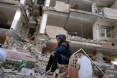 An earthquake survivor sits on debris in front of his house in a compound, which was built under the Mehr state-owned program, in Sarpol-e-Zahab in western Iran, Nov. 14, 2017.