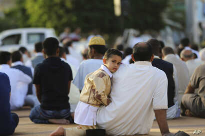 FILE - Worshipers attend a sermon during Eid al-Adha at the Martyrs Square in central Tripoli, Libya, -Sept. 24, 2015, in this photo by photographer and video journalist Mohamed Ben Khalifa, who was killed in Libya on Jan. 19, 2019.