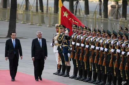 Sri Lankan Prime Minister Ranil Wickremesinghe (2nd L) and Chinese Premier Li Keqiang review an honor guard during a welcome ceremony outside the Great Hall of the People in Beijing on April 7, 2016.