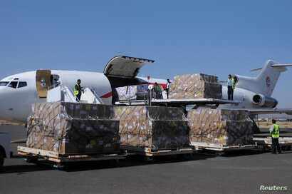 Workers unload aid shipment from a plane at the Sana'a airport, Yemen, Nov. 25, 2017.