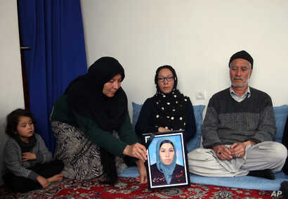 FILE - In this Jan. 28, 2016, photo, a relative holds a picture of Zainab Mirzaee, killed when the Taliban attacked a bus carrying employees of Afghanistan's biggest media company on Jan. 20.