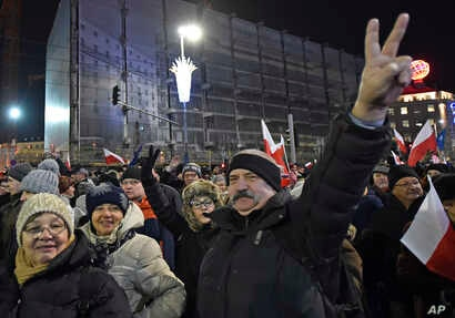 Anti-government protesters march through central Warsaw on the anniversary of imposition of the 1981 martial law by the country's former communist regime, in Warsaw, Poland, Tuesday, Dec. 13, 2016.