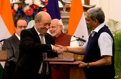 Indian Defense minister Manohar Parrikar shakes, right, hand with his French counterpart Jean-Yves Le Drian, second left, after exchanging the files of agreements on the buying of Rafale fighter jets as French President Francois Hollande, left, and I...