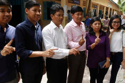 Voters show off their ink-stained fingers after casting their ballots at a polling station in Phnom Penh, Cambodia, July 29, 2018.