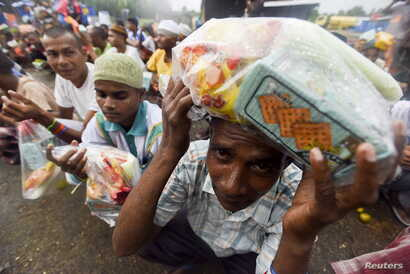 Rohingya migrants from Myanmar wait in line for food aid packages at a temporary shelter in Beyeun, in Indonesia's Aceh Province, May 31, 2015.