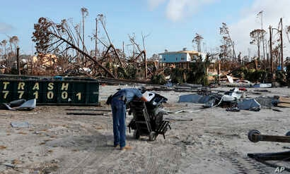 A man rests after pulling a dolly through sand as he helps retrieve belongings from his brother-in-law's destroyed home in the aftermath of Hurricane Michael in Mexico Beach, Florida, Oct. 17, 2018.