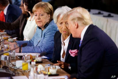 German Chancellor Angela Merkel watches as President Donald Trump talks with IMF Managing Director Christine Lagarde during the Gender Equality Advisory Council breakfast during the G-7 summit in Charlevoix, Canada, June 9, 2018.