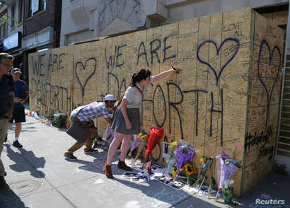 People write messages on construction boarding after a mass shooting on Danforth Avenue in Toronto, Canada, July 24, 2018.