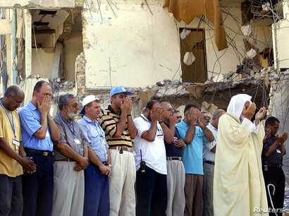 FILE - U.N. staff are led in prayer by an Imam in front of the devastated former U.N. headquarters in Baghdad, during a memorial service on Aug. 30, 2003. The bomb on Aug. 19 killed 22 people, including U.N. envoy Sergio Viera de Mello.