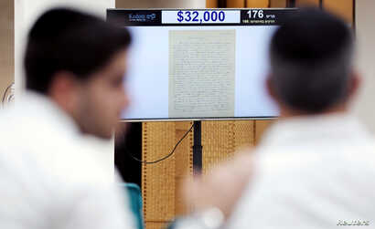 People attend a public auction where a letter written in 1922 by physicist Albert Einstein is put up for sale at Kedem Auction House in Jerusalem, Nov. 13, 2018.