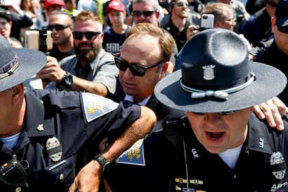 FILE - Alex Jones (C), an American conspiracy theorist and radio show host, is escorted out of a crowd of protesters after he said he was attacked in Public Square on July 19, 2016, in Cleveland, during the second day of the Republican convention.